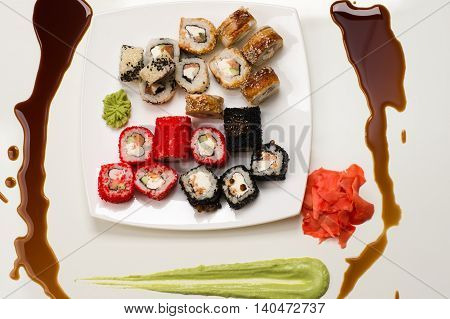 assorted rolls, ginger, wasabi and soy sauce on white background