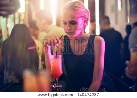 Blonde woman in a club drinking a cocktail