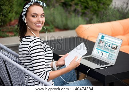 Emotionally charged. Delighted smiling beautiful woman sitting at the table and expressing gladness while listening to music