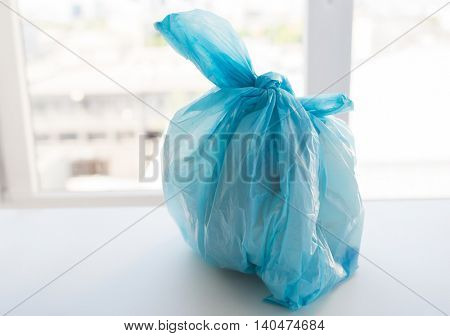waste recycling, reuse, garbage disposal, environment and ecology concept - close up of rubbish bag with trash or garbage at home