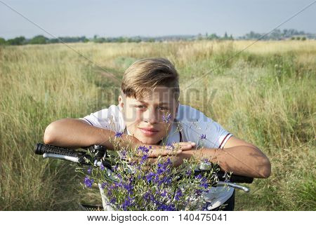 happy boy with a bicycle, in a basket of wildflowers