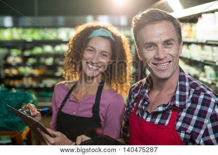 Portrait of smiling staffs writing on clipboard in organic section of supermarket