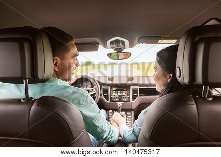leisure, road trip, travel and people concept - happy man and woman driving in car and looking back