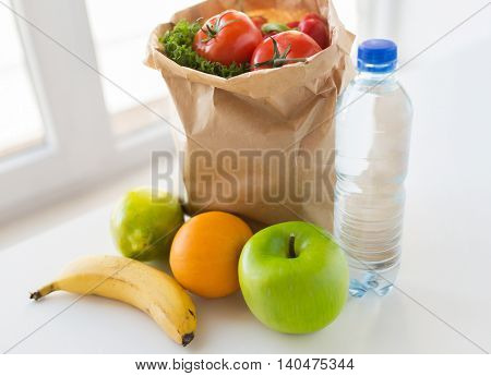 cooking, diet, vegetarian food and healthy eating concept - close up of paper bag with fresh ripe juicy fruits and vegetables and water bottle on kitchen table at home