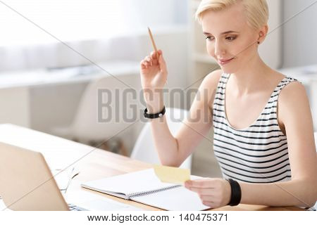 Extremely satisfied. Contented woman looking at the screen of the laptop while checking some information and holding a piece of paper