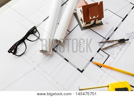 architecture, building, construction, real estate and home concept - close up of blueprint with living house model and tools