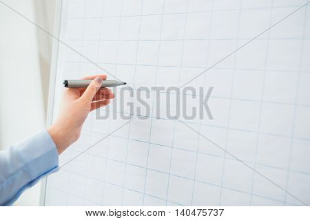 office, business, people and education concept - close up of hand with marker writing or drawing something on flip chart