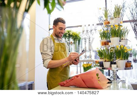 people, sale, retail, business and floristry concept - happy smiling florist man with bunch writing and making notes to clipboard at flower shop counter