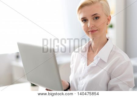 Like what you do. Elegant young woman looking at the camera while standing and holding a laptop