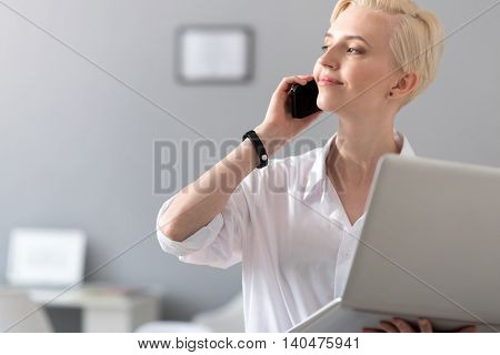 I am good at managing. Delighted middle aged woman having a conversation on the phone while holding an open laptop and looking aside