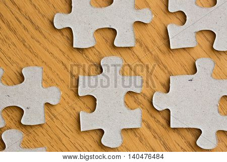 business and connection concept - close up of puzzle pieces on wooden surface