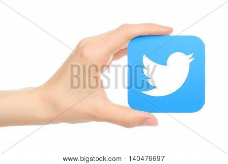 Kiev Ukraine - May 18 2016: Hand holds twitter icon printed on paper. Twitter is an online social networking service that enables users to send and read short messages