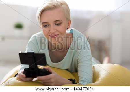 It is an addiction. Pleasant good looking woman lying on the bean bag and playing games on her smartphone with clipping path for screen