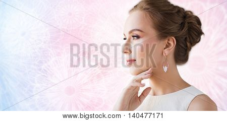 jewelry, luxury, wedding and people concept - smiling woman in white dress wearing pearl earring over rose quartz and serenity patterned background