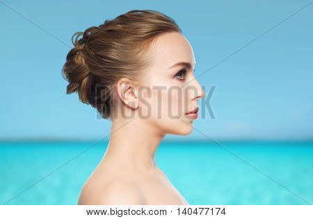health, people, plastic surgery and beauty concept - beautiful young woman face over blue sea and sky background