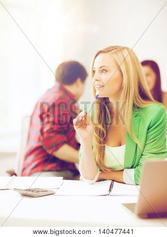 education concept - student girl with notebook and calculator in college