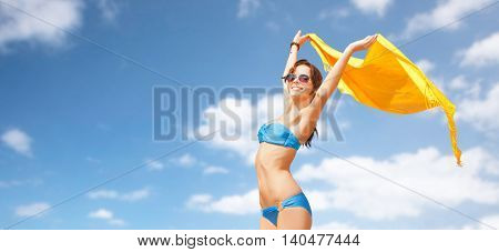 people, summer holidays and vacation concept - beautiful woman in bikini and sunglasses with pareo over blue sky and clouds background