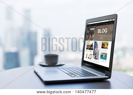 technology, business, mass media, internet and modern life concept- close up of open laptop computer with blog web page on screen and coffee cup on table at office or hotel room
