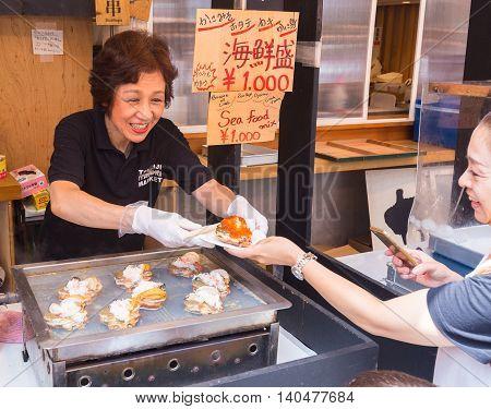TOKYO JAPAN - 18 JULY 2016 - Happy smiling woman seller sells seafood dish to her customer at Tsukiji Fish Market in Tokyo Japan on July 18 2016.