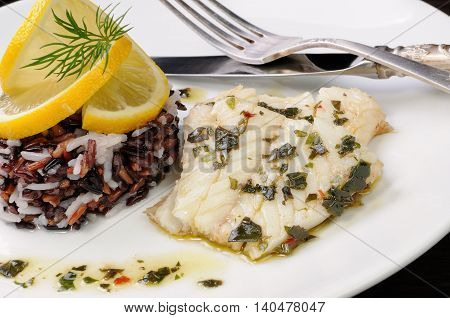 Slices of boiled fish with pesto and black brown white rice