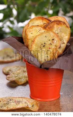Homemade potato chips wrapped in paper and folded bucket