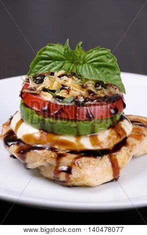 Chicken breast with slices of mozzarella avocado tomato and basil
