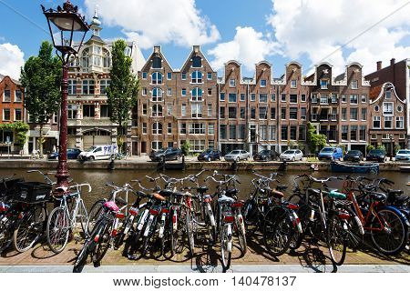 Amsterdam Netherlands - July 03 2016: Bicycle parking on the background of the traditional Amsterdam houses summer time