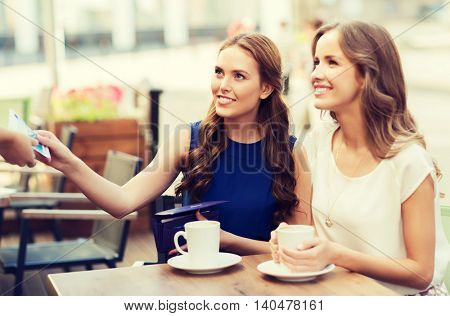people, consumerism, lifestyle and friendship concept - smiling young women giving money to waiter hand and paying for coffee at outdoor cafe