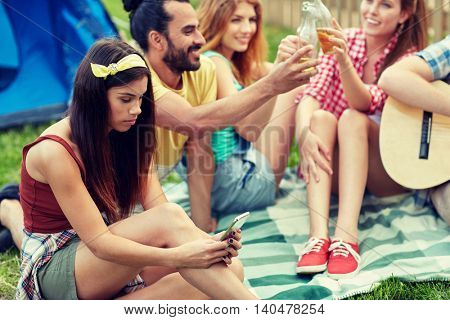 travel, tourism, hike, technology and people concept - young woman with smartphone and friends at camping