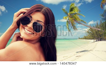 summer vacation, tourism, travel, holidays and people concept -face of smiling young woman with sunglasses over tropical beach background