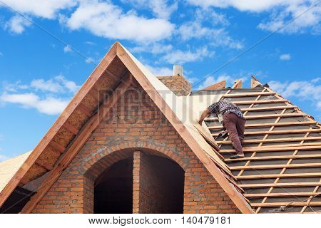 House under construction. Workers installing fibreboard on the roof