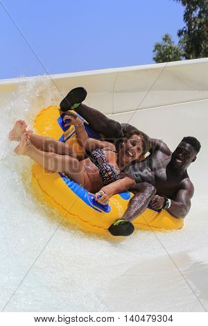 Rhodes Greece-July 2 2016:Boyfriend and a Girlfriend in a very interesting way drive with tube on the rafting slide in the Water park.Rafting slide is one of many popular game for adults and children in park.Water Water Park is located in Faliraki
