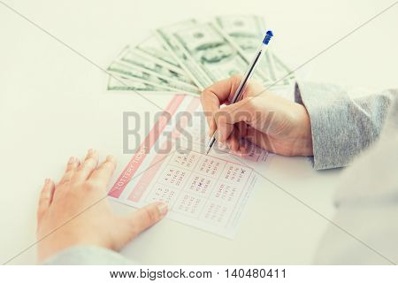 business, finance, gambling and people concept - close up of woman hands filling lottery ticket and us dollar money
