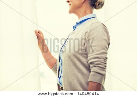 age and people concept - close up of happy smiling senior woman looking through window at home