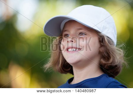 Little cute girl with a cap in the park happy