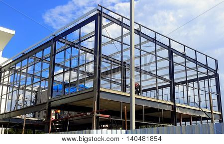 steel frame, two-story building being built at a construction site, with blue sky and clouds, Songkhla, Thailand