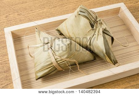 Chinese Cuisine Zongzi or Sticky Rice Dumpling in A Wooden Tray for Dragon Boat Festival.