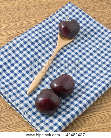 Fresh Fruits Ripe and Sweet Red Plums A Very Good Source of Vitamin C on Blue and White Checked Towel.