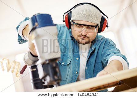 Carpenter at work.Safety-conscious contractor or homeowner working with nail gun