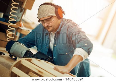 Carpenter working on a plank of wood in his workshop.