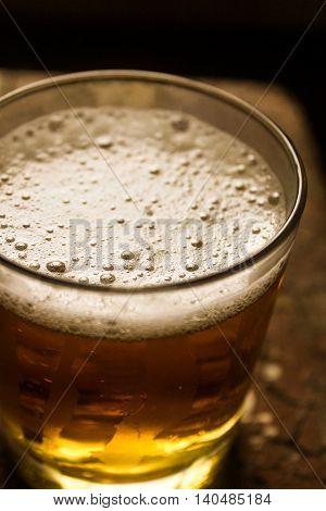 Glass of light beer on a dark pub.