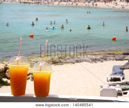 Two fresh orange juice in a plastic cup with straws on sea background
