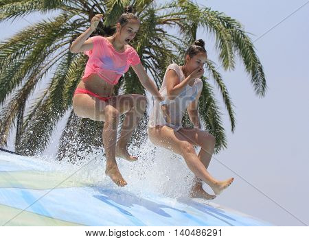 Rhodes Greece-Jun 27 2016:Two girls have a fun jumping on the wet bubble in the water park .Wet bubble is one of many popular game for adults and children in Water park..Water Park is located in Faliraki on the island of Rhodes in Greece and one of