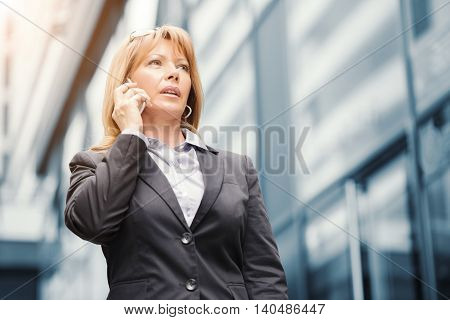 Businesswoman on the phone outdoors.She is in front of office buildings.
