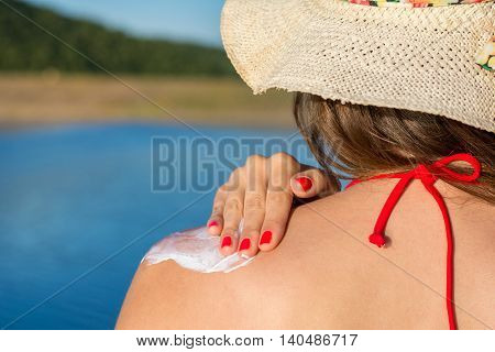 Young Woman Putting Sun Lotion On Summer Vacation