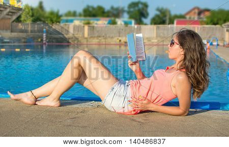 Girl Reading A Book By The Pool.
