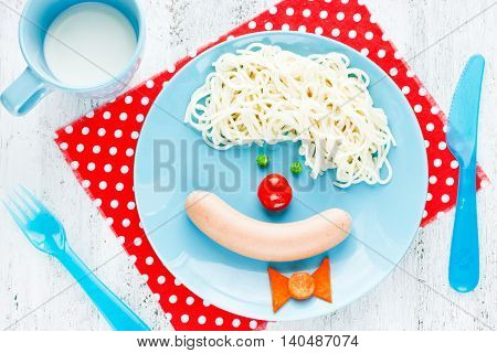 Creative breakfast or lunch for children - spaghetti with sausage and vegetables in the form of a funny clown face