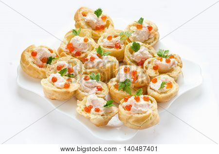 Profiteroles with mousse or pate and red caviar on white background. Cocktail party snacks with red caviar gourmet food festive appetizer