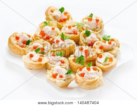 Profiteroles with mousse or pate and red caviar on white background. Cocktail party snacks with red caviar gourmet food