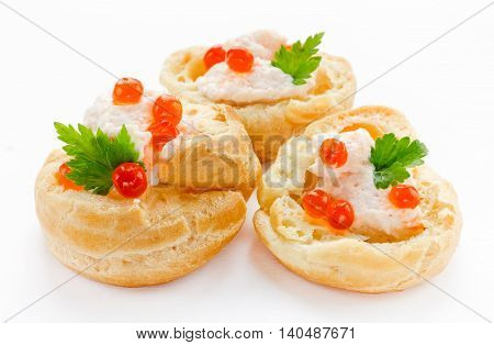 Profiteroles with fish mousse or pate and red caviar close up isolated on white background. Snack with red caviar gourmet food party appetizer